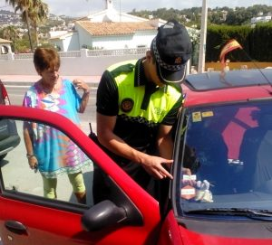 Un policia local de Benissa enganxa l'adhesiu a un vehicle d'una resident